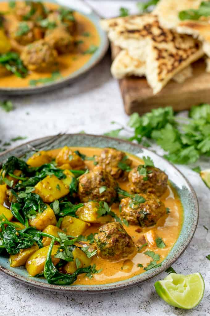 Beef Kofta with saag aloo on a plate. Cilantro and naan bread in the background