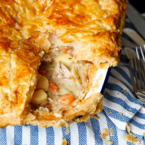 A dish of creamy chicken pie with puff pastry sat on a blue and white striped cloth.