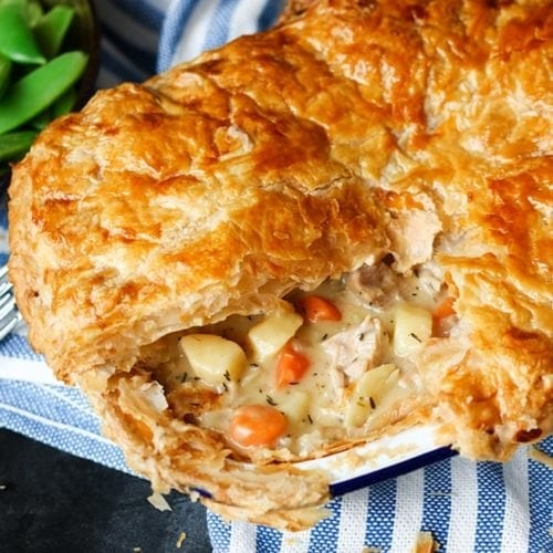 Chicken pie with slice taken out on a blue and white striped tea towel