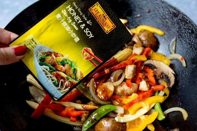Adding stir fry sauce to chicken and vegetables in a wok