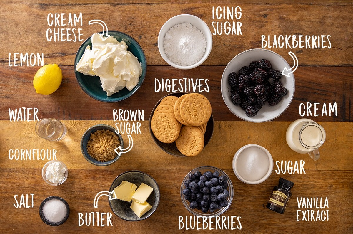 Ingredients for individual mason jar cheesecakes on a wooden table