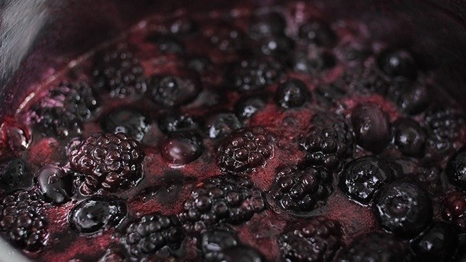 Blueberries and blackberries simmering in pan