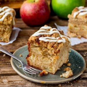 Square image of a slice of apple streusel cake with vanilla icing