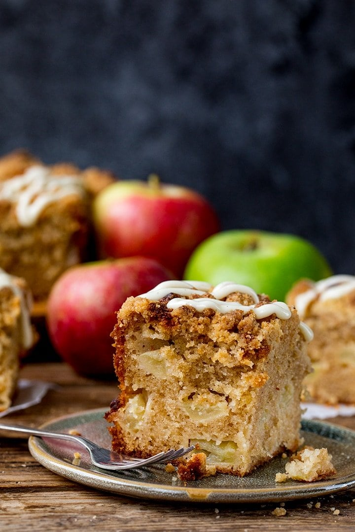 apple streusel cake on a green plate. Apples in the background
