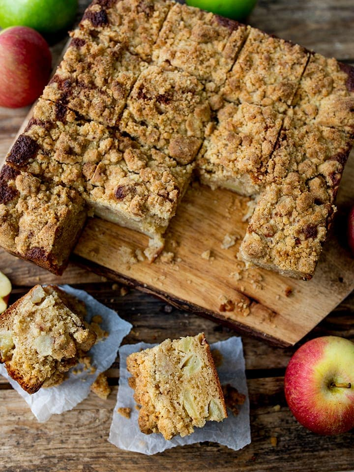 apple crumble cake on a chopping board, sliced into squares
