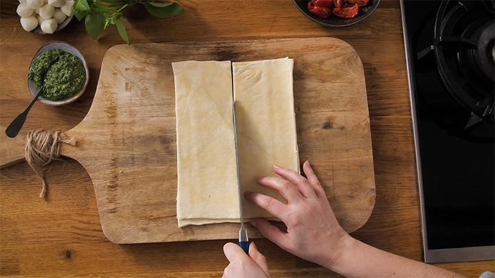 Slicing raw puff pastry into squares for caprese pastry bites