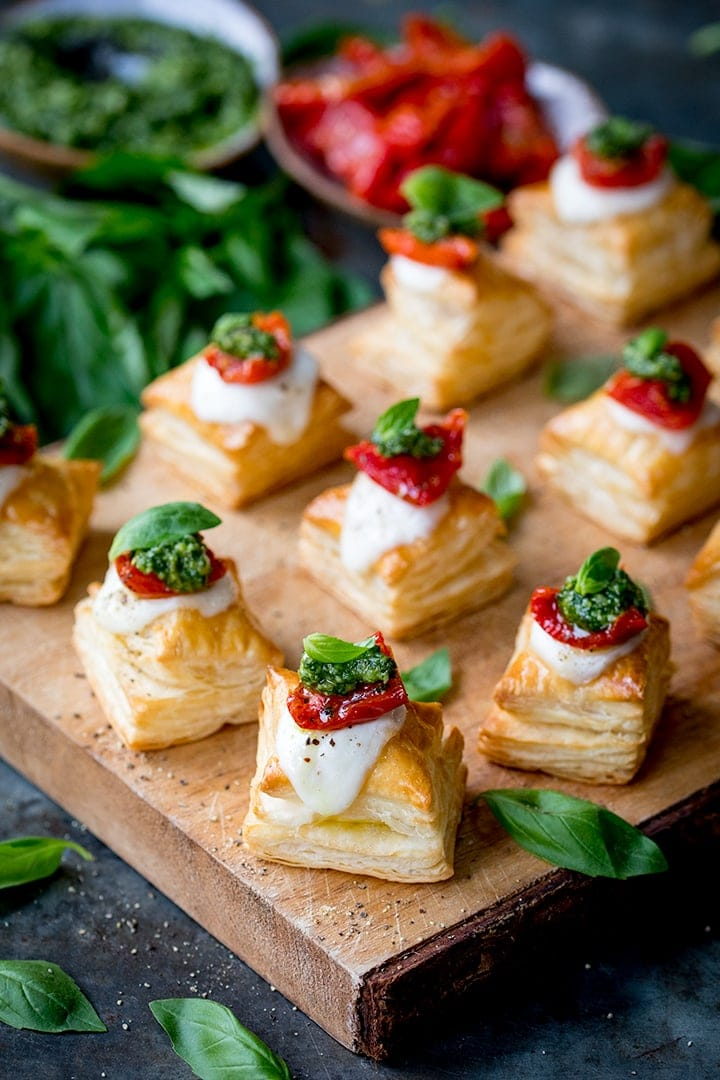 Puff pastry caprese bites - with mozzarella, pesto and sundried tomato - on a serving board