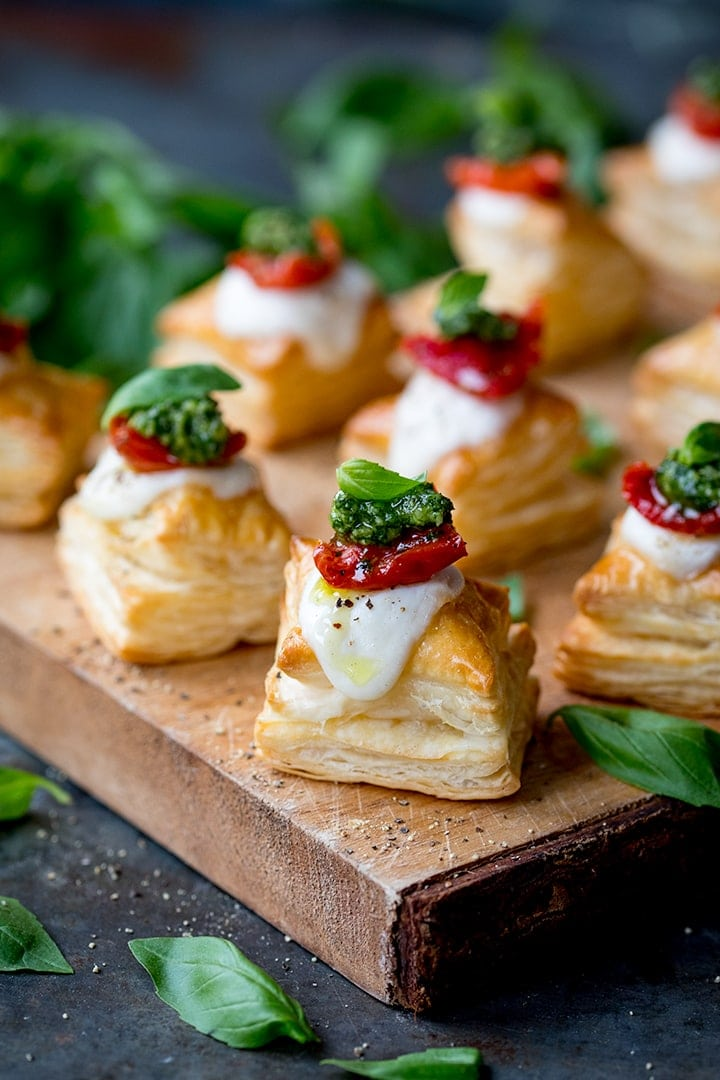 Close up of puff pastry caprese bites - with mozzarella, pesto and sundried tomato - on a serving board
