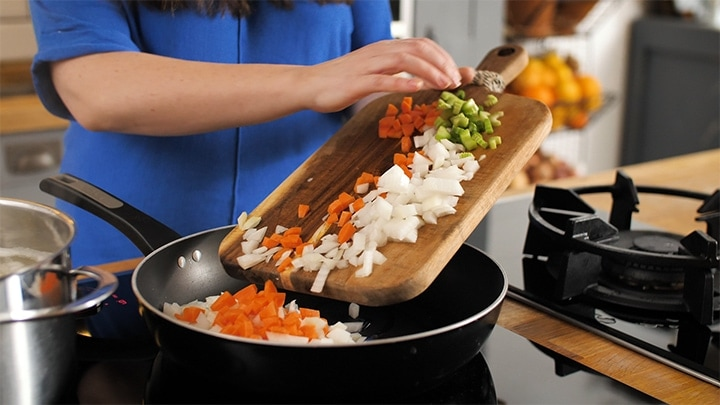 Placing chopped onions, carrot and celery in a pan for cottage pie
