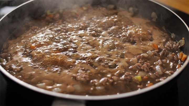 Minced beef and gravy bubbling in a pan