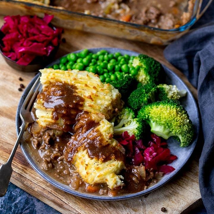 Cottage pie on a plate with broccoli, peas and red cabbage