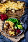 Cottage pie on a plate with gravy, broccoli, peas and red cabbage