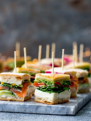 Pressed mini sandwich bites with different fillings on a marble platter