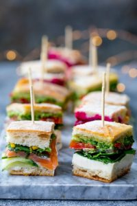 Mini sandwich bites with different fillings on a marble platter