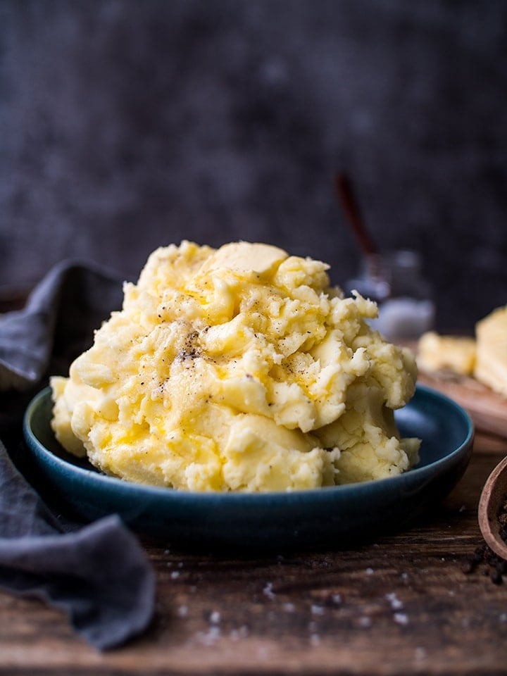 Mashed potatoes in a blue bowl on a wooden table
