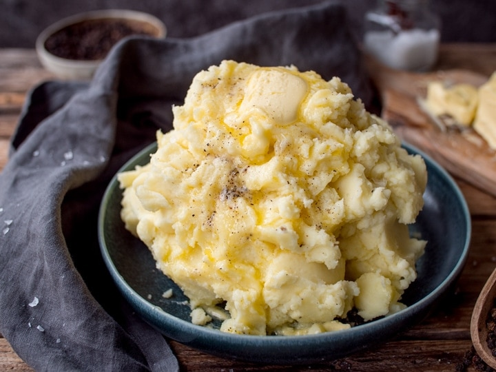 Wide image of mashed potatoes in a blue bowl.