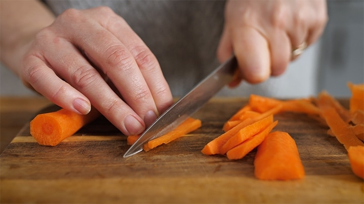 Carrots being sliced on a chopping board