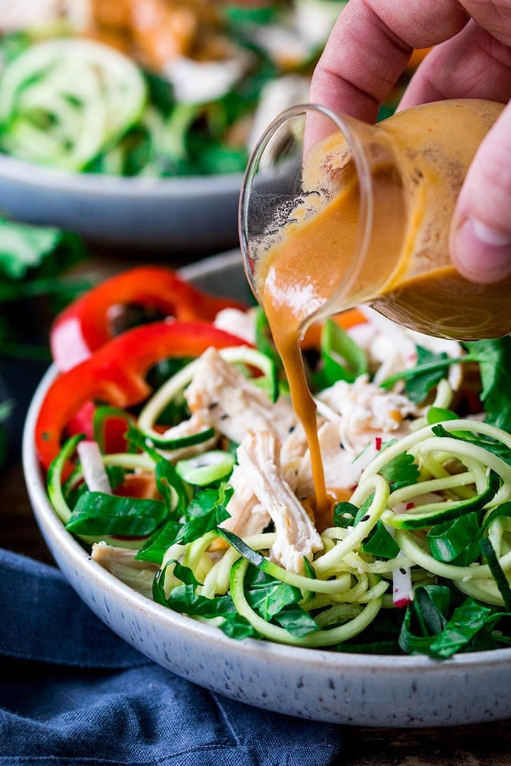 Thai peanut sauce being poured on chicken zoodle salad
