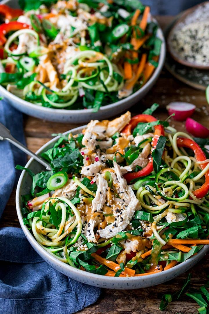 chicken zoodle salad in a bowl with Thai peanut sauce