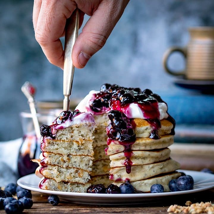 Forkful of Chia hazelnut pancakes with blueberry compote being taken