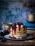 Stack of chia hazelnut pancakes on a plate with greek yogurt and blueberry compote dripping down