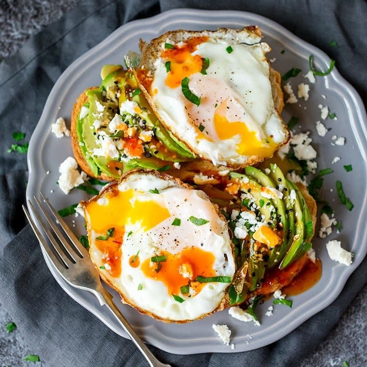 Square image of avocado and eggs on toast with feta and sweet chilli sauce