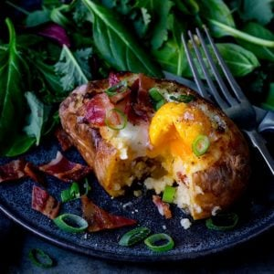 Square image of egg and bacon stuffed baked potato with runny egg on a dark plate