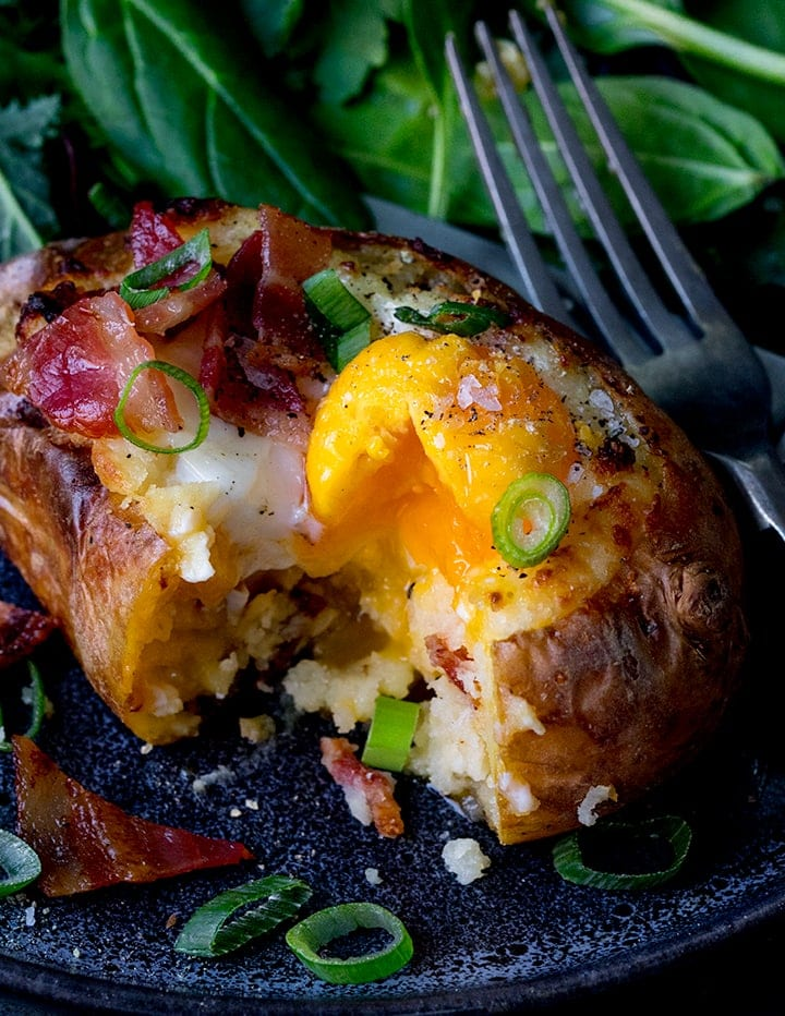 Close up of baked potato stuffed with baked egg and bacon