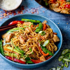 chicken lo mein in blue bowl on a blue background