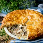 Square image of chicken and mushroom pie with a slice taken out
