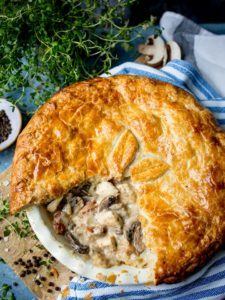 Overhead image of chicken and mushroom pie with a slice taken out