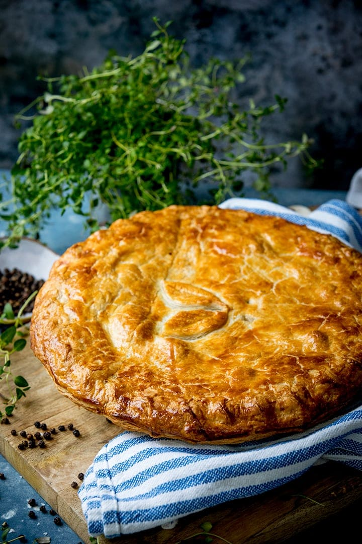 chicken and mushroom pie on a wooden table with a blue and white striped tea towel