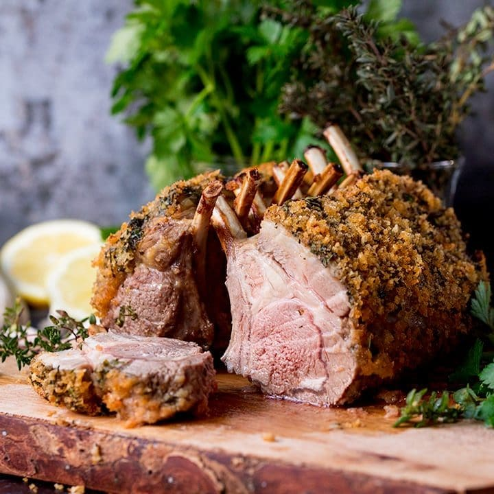 Square image of Herb crusted roasted rack of lamb with a slice taken out