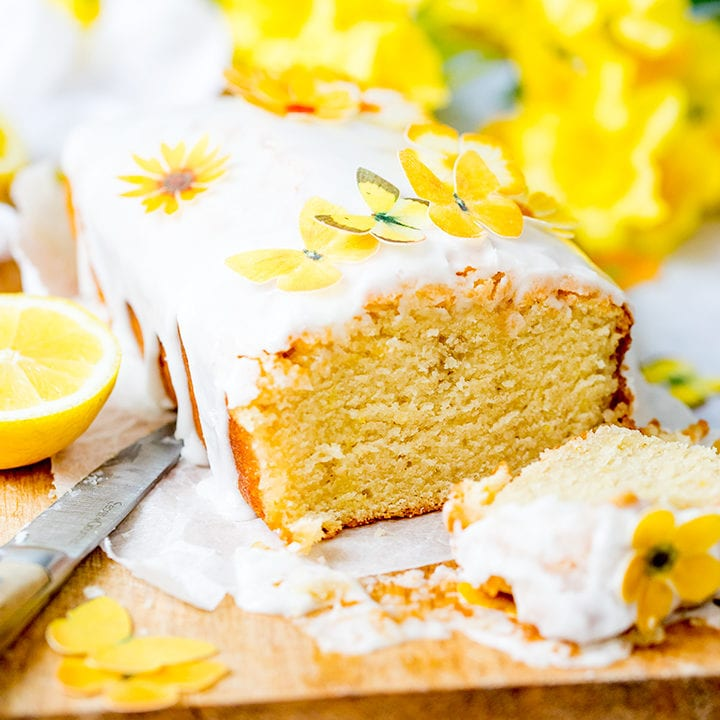 Square image of sliced open lemon drizzle cake