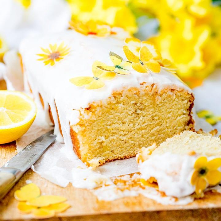Square image of sliced open lemon drizzle cake