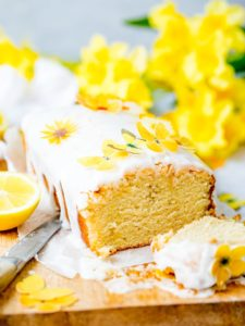 Sliced vegan lemon drizzle cake with white icing on yellow sugar flowers on a wooden board