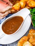 Beef gravy in white jug surrounded by beef and potatoes