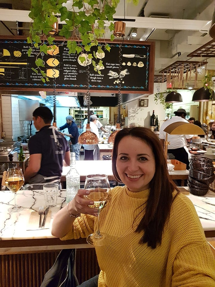 Nicky holding a glass of wine in Eataly in New York