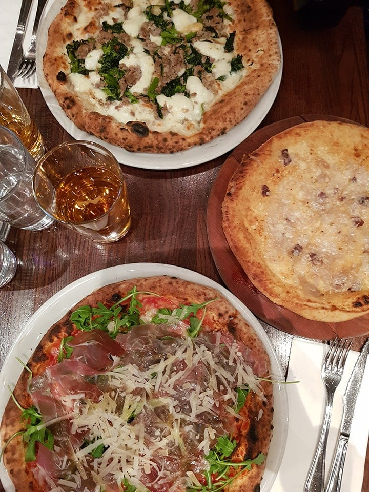 Three pizzas on a table at Don Antonio's New York