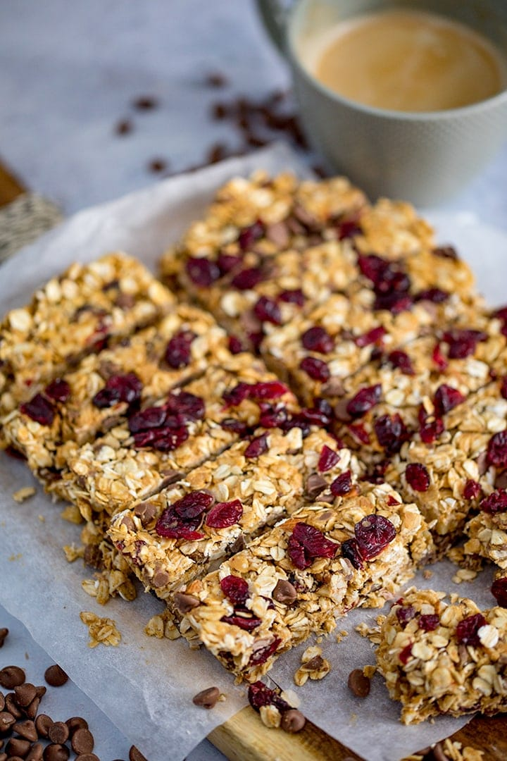 Peanut Butter Granola Bars with cranberries and chocolate chips on a chopping board