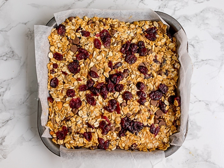 Granola bar mixture in a baking tin on white background