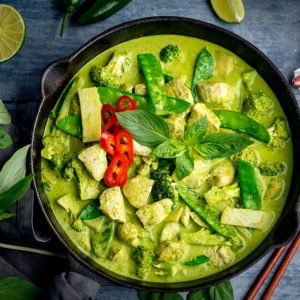 Square image of Pan of Thai green chicken curry with vegetables on blue background