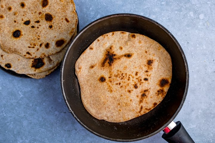 Chapati frying in a pan on a blue background