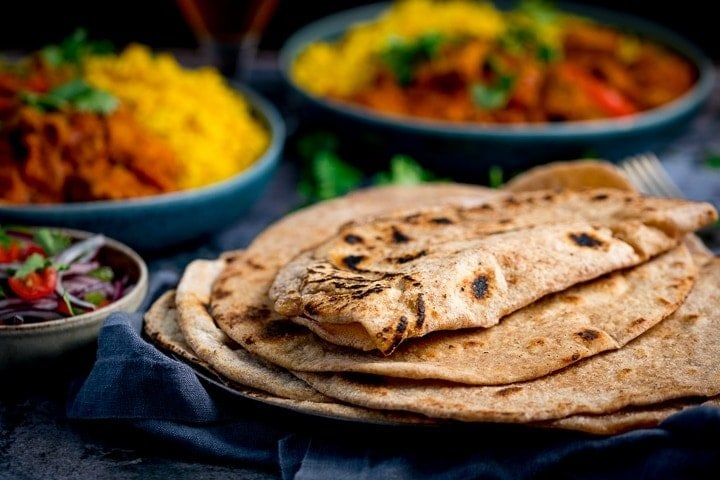 wide image of Chapati on a plate with dishes of curry in the background