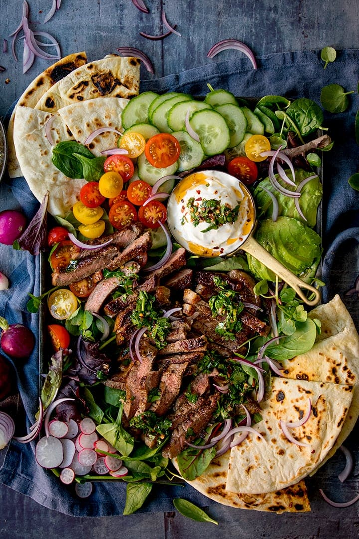 Overhead image of a large salad platter with strips of steak, chimichurri sauce and flatbreads on a blue background