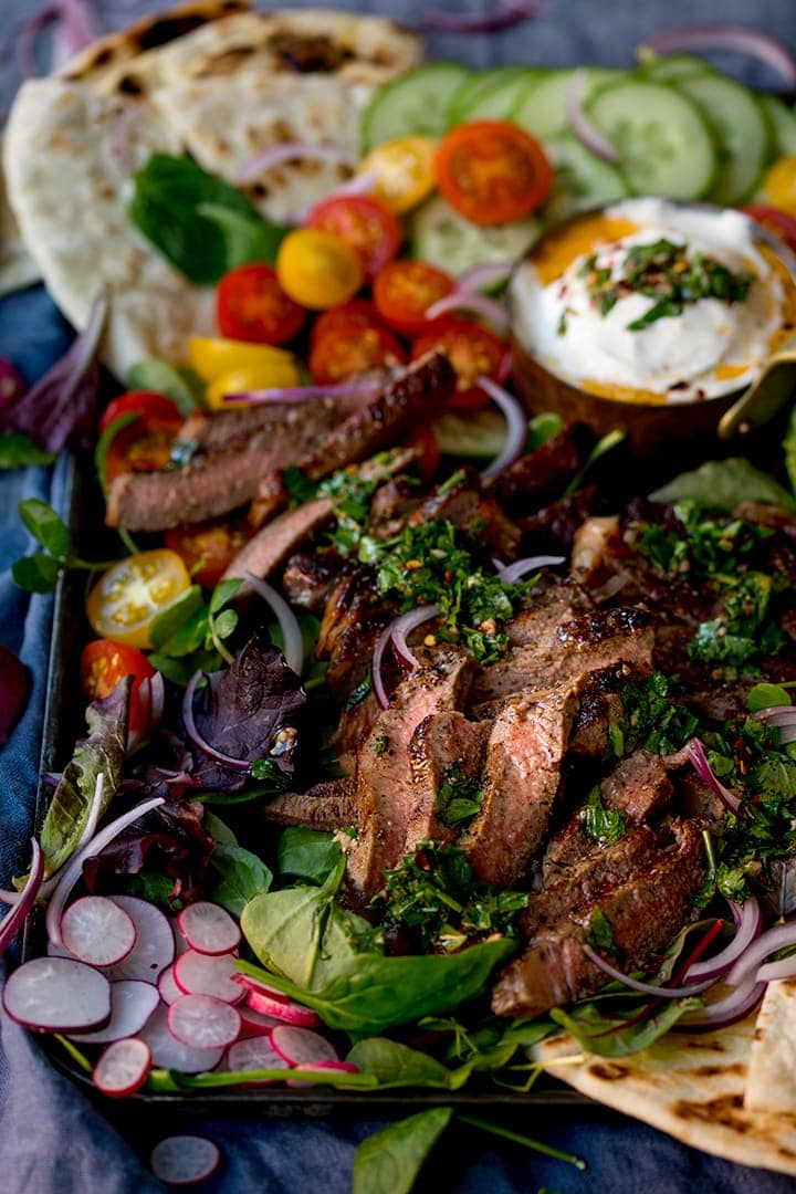 Close up image of chimichurri steak salad platter on a dark background