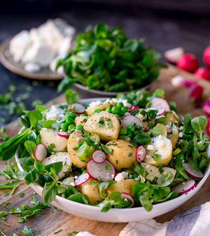 Green salad with new potatoes, radish slices and herb dressing in a white bowl