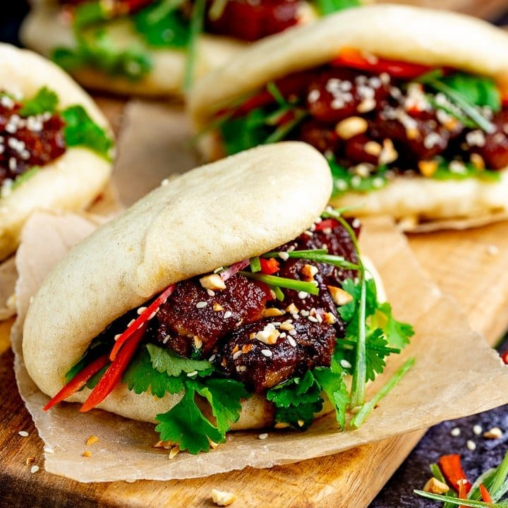 Gua Bao pork belly buns on a wooden board with another one in the background