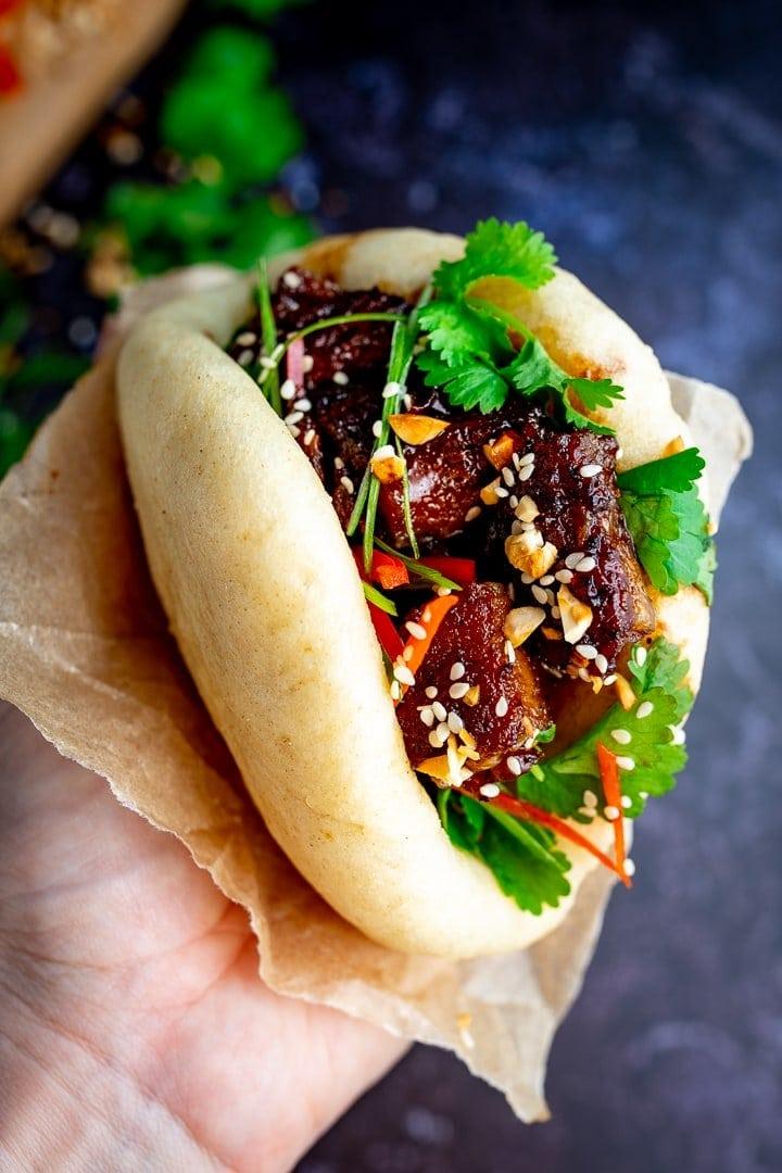 Hand holding Gua Bao pork belly bun