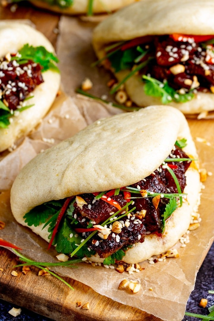 Gua Bao pork belly buns with coriander and spring onions on a wooden board